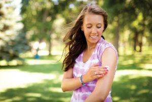 cancer survivor Megan McManus applies sunscreen to her arm